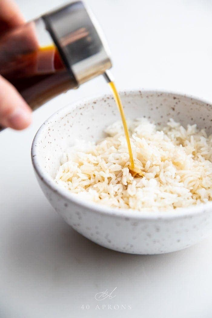 A bottle of soy sauce substitute pouring over a bowl of white rice