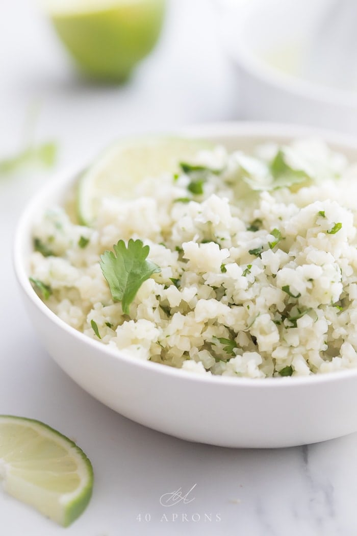 A white bowl of cilantro lime cauliflower rice with limes and juicer in background
