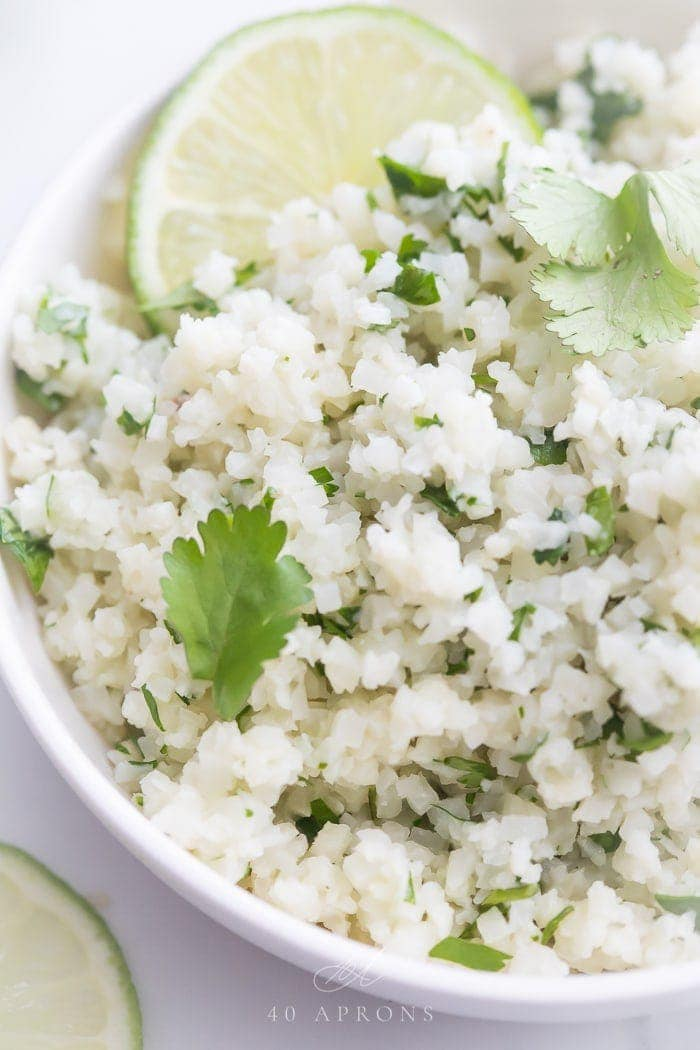 A white bowl of cilantro lime cauliflower rice with cilantro and lime garnishes