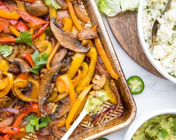 Overhead of Vegetarian sheet pan fajitas with a bowl of cauliflower rice and bowl of guacamole to the side