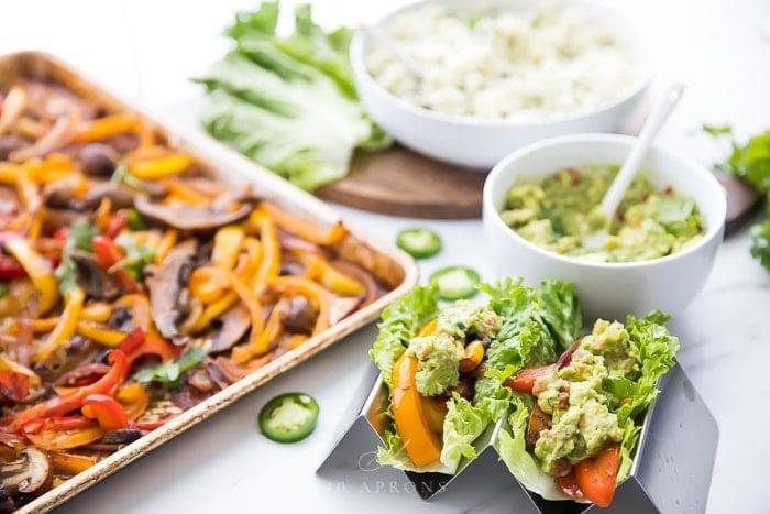 Vegetarian sheet pan fajitas in lettuce wraps next to the pan, a bowl of cauliflower rice, and bowl of guacamole