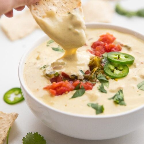 Hand dipping a tortilla chip into a bowl of vegan queso topped with tomatoes and jalapenos