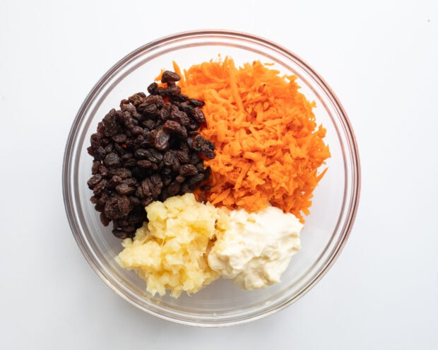 Ingredients for carrot raisin salad in one glass bowl