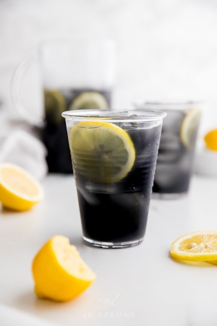 A glass of black charcoal lemonade with lemon slice, with glass and pitcher in background