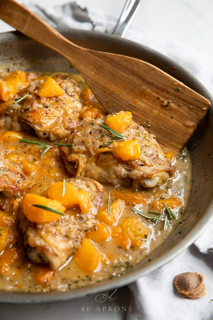 Apricot chicken in an ovenproof skillet with a wooden spoon