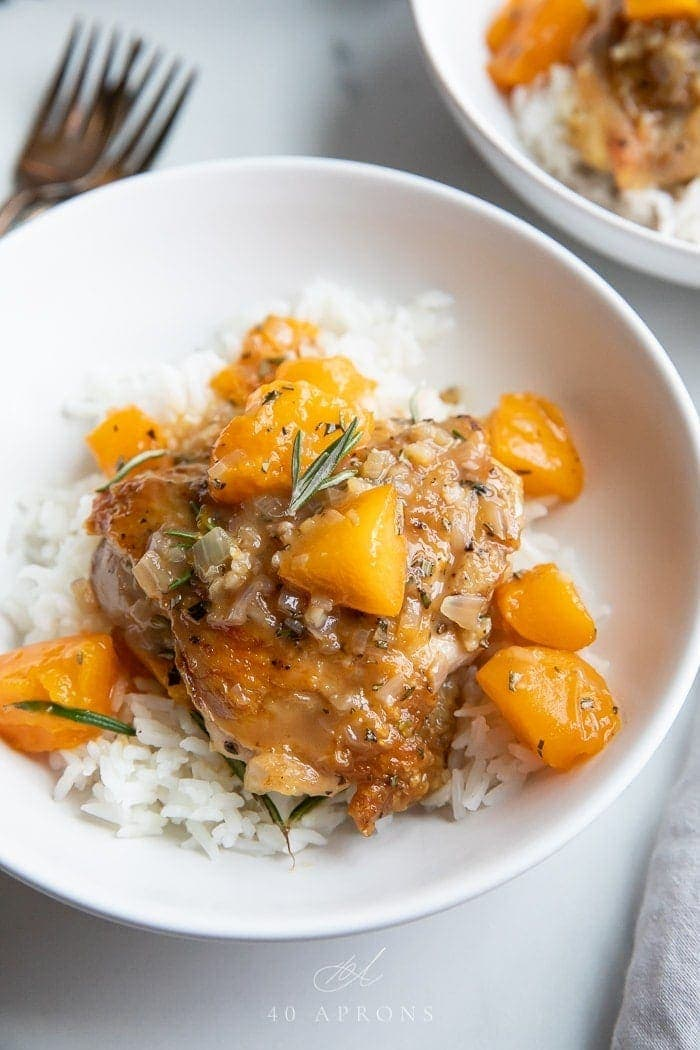 Apricot chicken over white rice in a white bowl