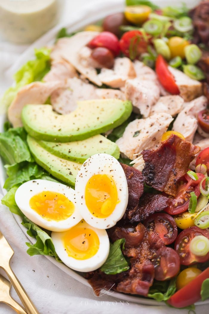 Close up on soft boiled eggs and bacon on classic chicken cobb salad