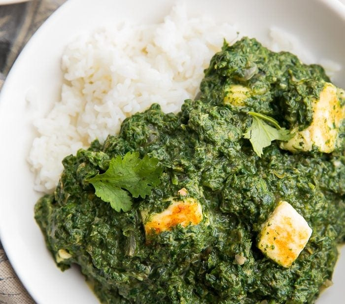 A bowl of palak paneer over rice
