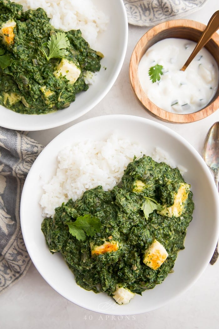 Two bowls of palak paneer over rice with raita on the side