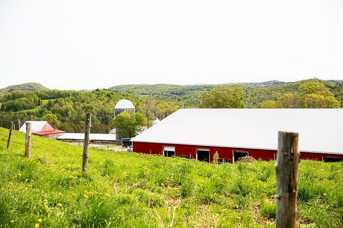 A landscape of Vermont with a red barn and silo