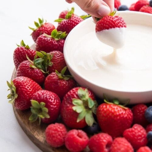 A bowl of yogurt fruit dip with a strawberry dipping in it