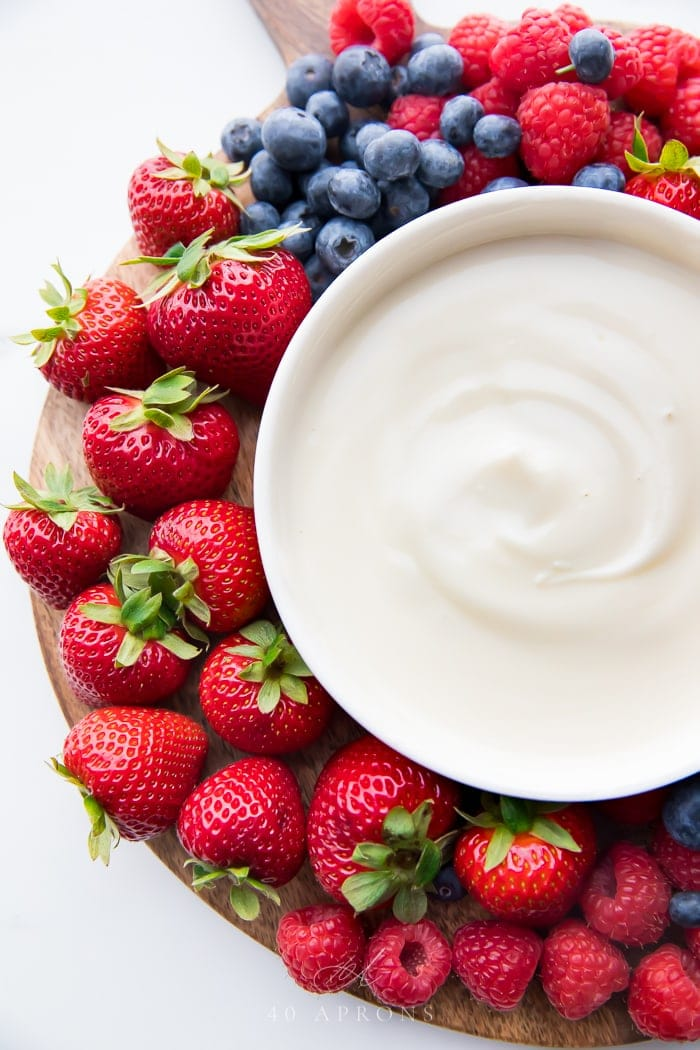A tray of berries with bowl of yogurt fruit dip in the center