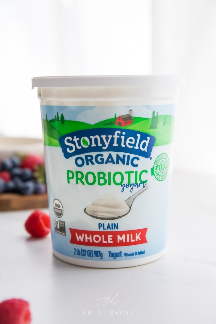 A container of Stonyfield Organic Plain Whole Milk Yogurt with berries in background