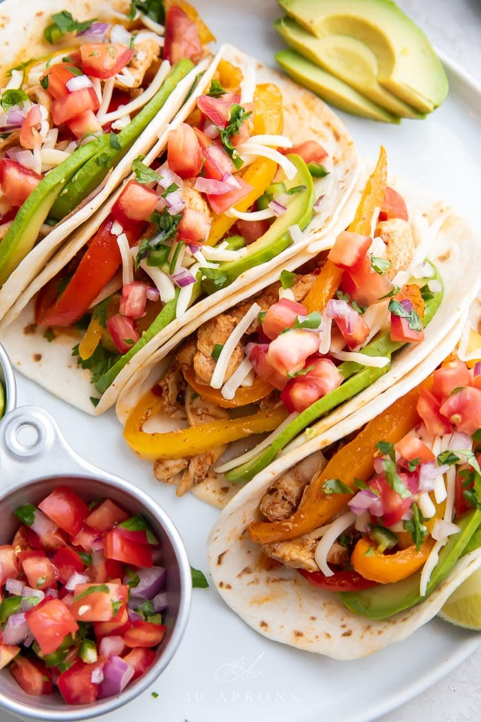 Tacos served on a white plate with salsa