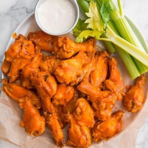 Crockpot chicken wings on parchment paper with celery and blue cheese