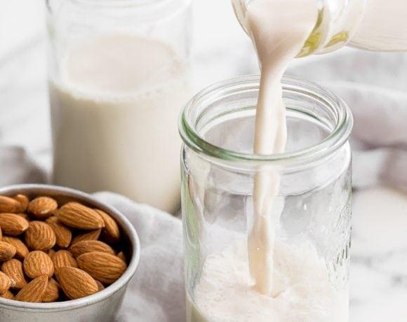 Homemade almond milk pouring into a jar