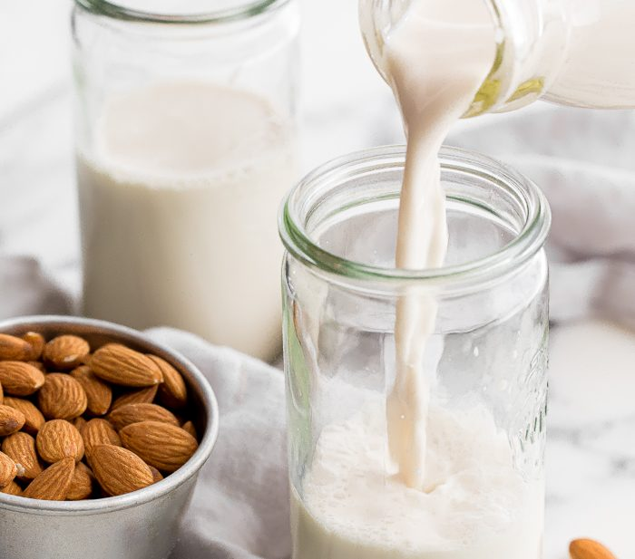 Homemade almond milk pouring into a jar