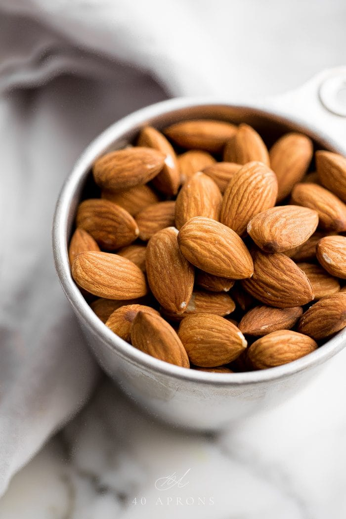 Silver measuring cup of almonds