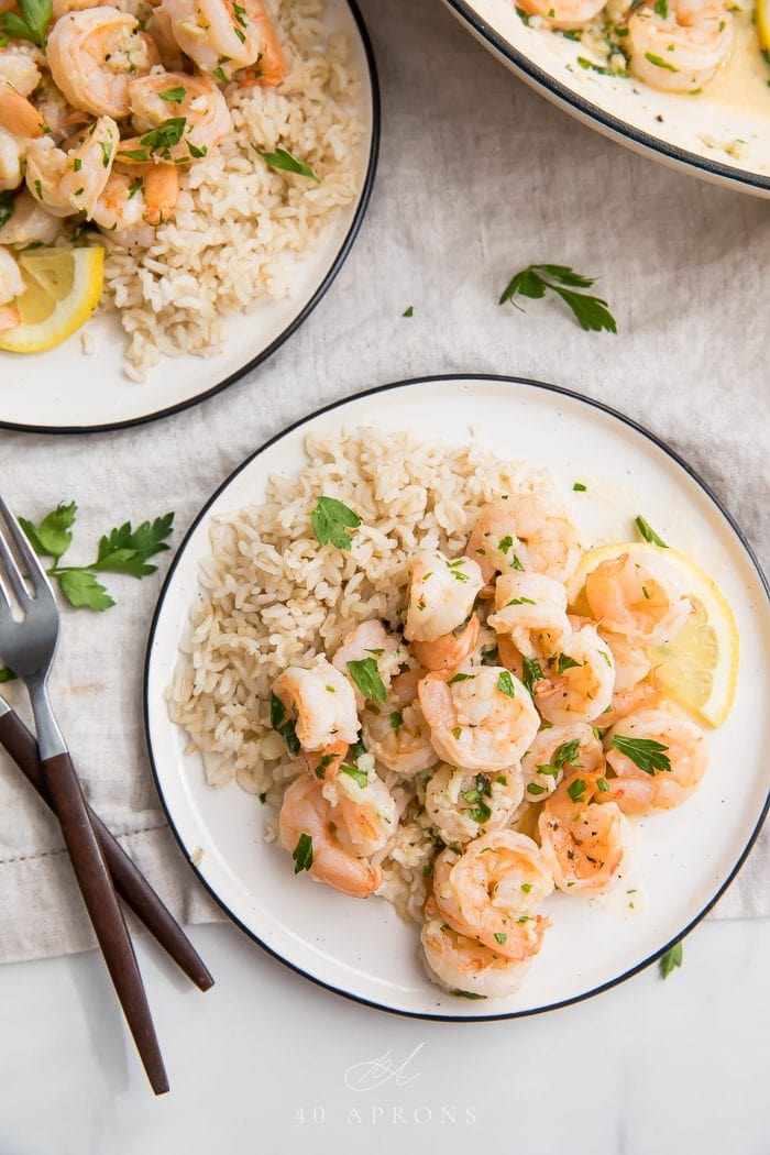 Two plates of lemon garlic shrimp with brown rice