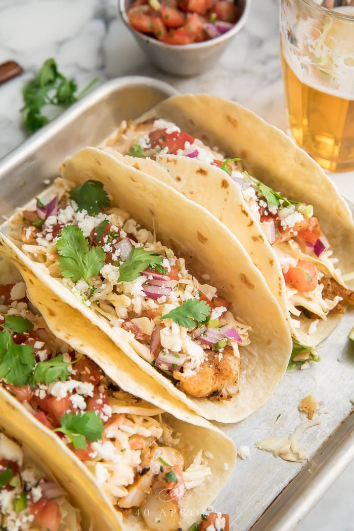 Three easy fish tacos on a metal tray with fresh herbs