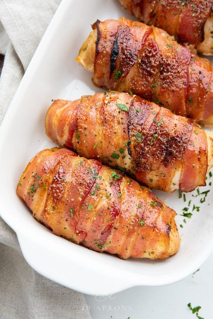 Four Bacon wrapped chicken breasts in a baking dish