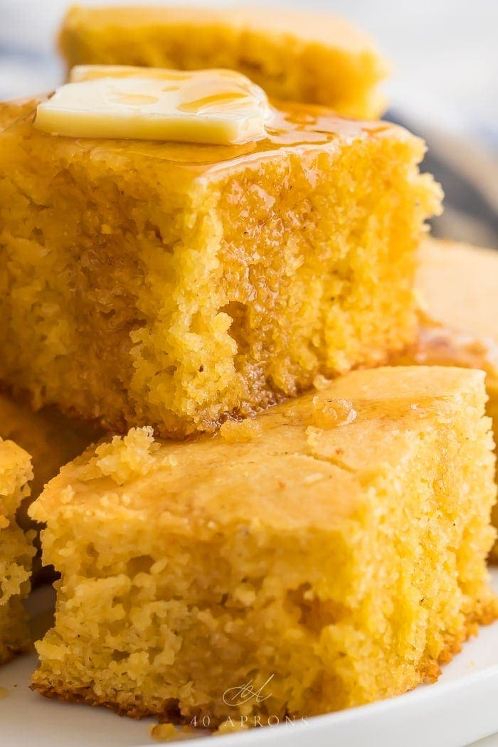 Gluten free cornbread stacked on a white plate with butter and honey