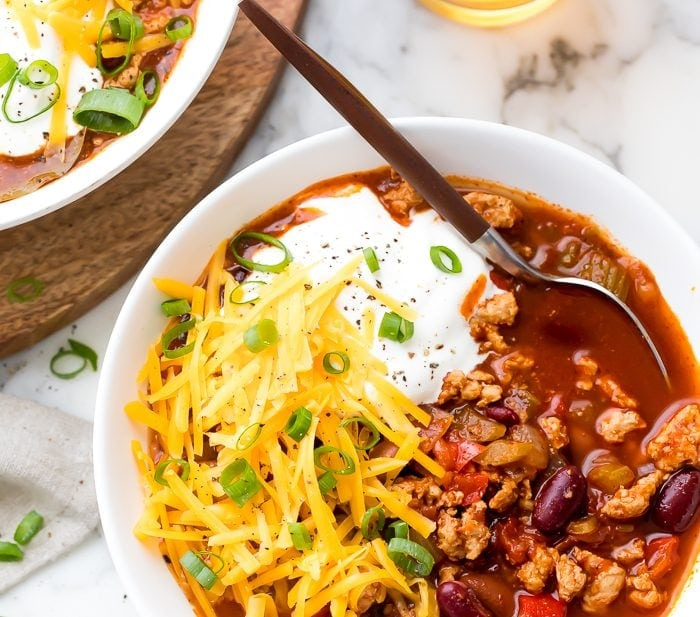Turkey chili served in a white bowl with toppings