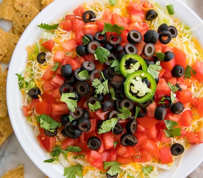 Taco dip in a white dish with tortilla chips around