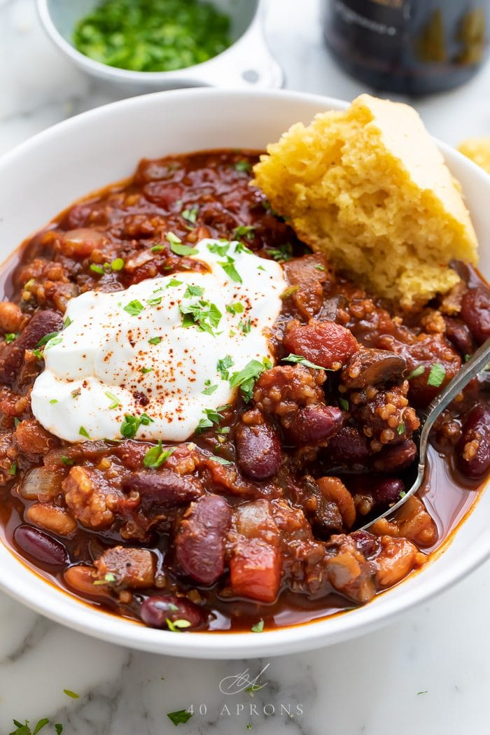 Chili served in a bowl with a spoon and piece of cornbread
