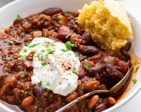 A bowl of vegan chili with a piece of cornbread