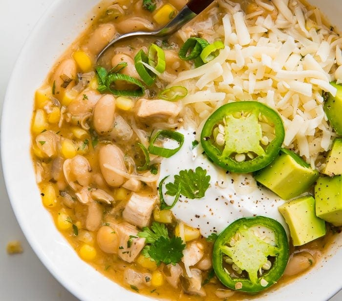 white bean chili in a white bowl with fresh toppings