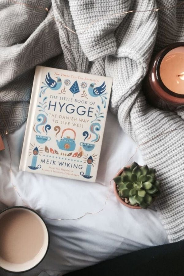 overhead shot of The Little Book of Hygge by Meik Wiking lying on a bed with a lit scented candle and a mug of coffee on the side