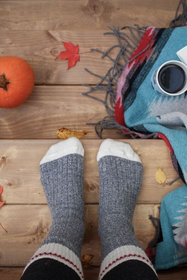 woman's feet in thick socks standing on a rustic wooden floor between a pumpkin, a scarf and a mug of coffee