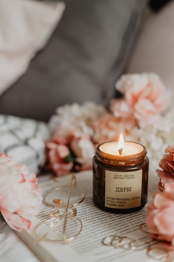 a scented candle on an opened book with golden glasses on the side and flowers in the background