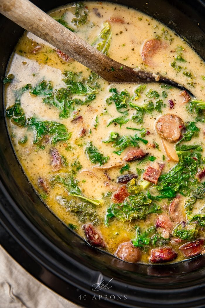 A spoon stirring the zuppa toscana in the crockpot