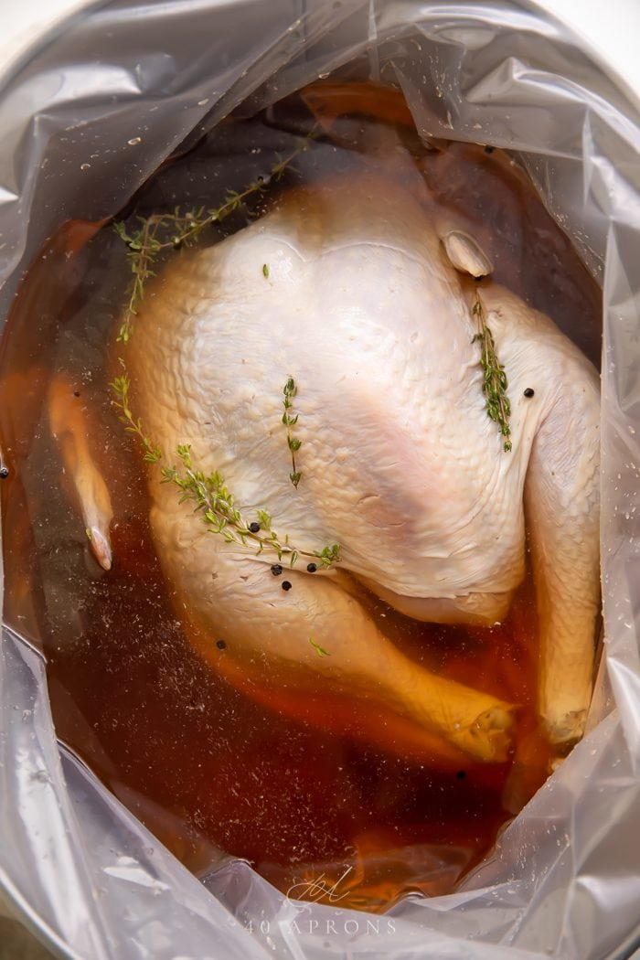 A turkey brining in a large container
