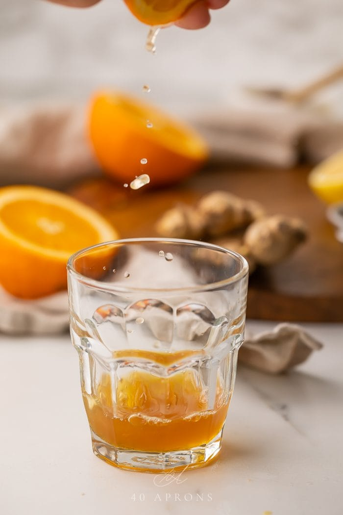 Orange juice being squeezed into an immune booster shot recipe glass