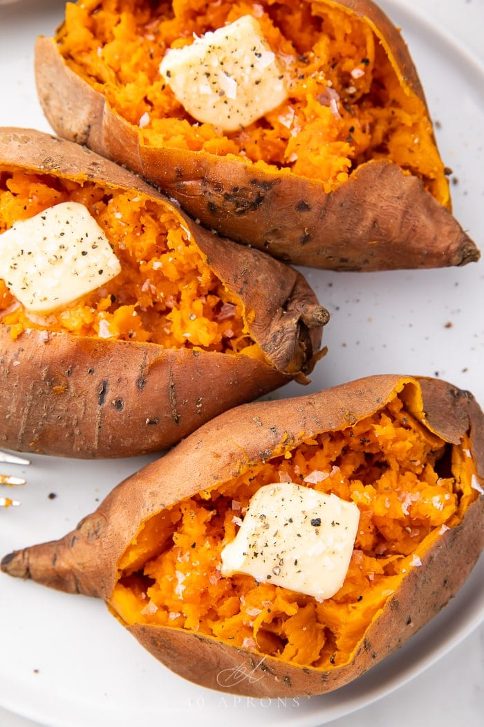 Three cooked sweet potatoes on a white plate
