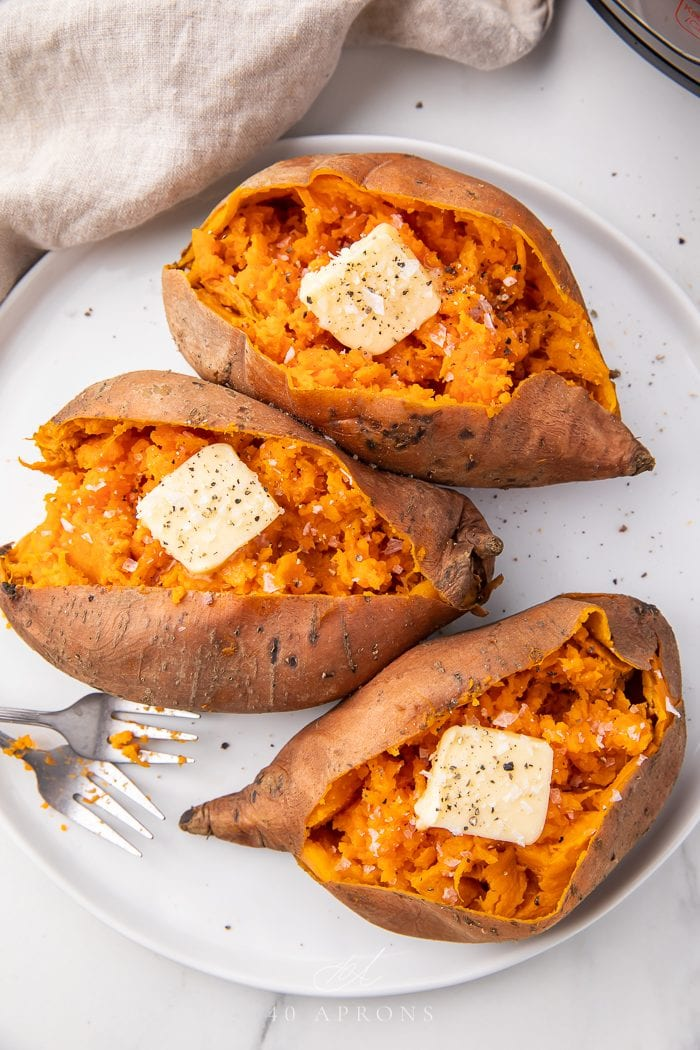 Three sweet potatoes on a plate with butter
