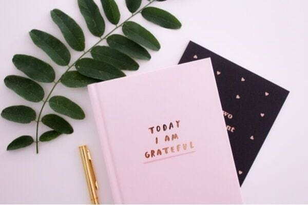 a gratitude journal with a golden pen on the side