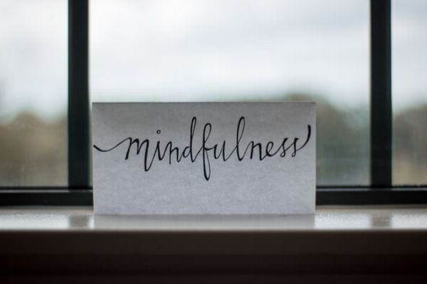 a small piece of paper with the word mindfulness written on it leaning against a window