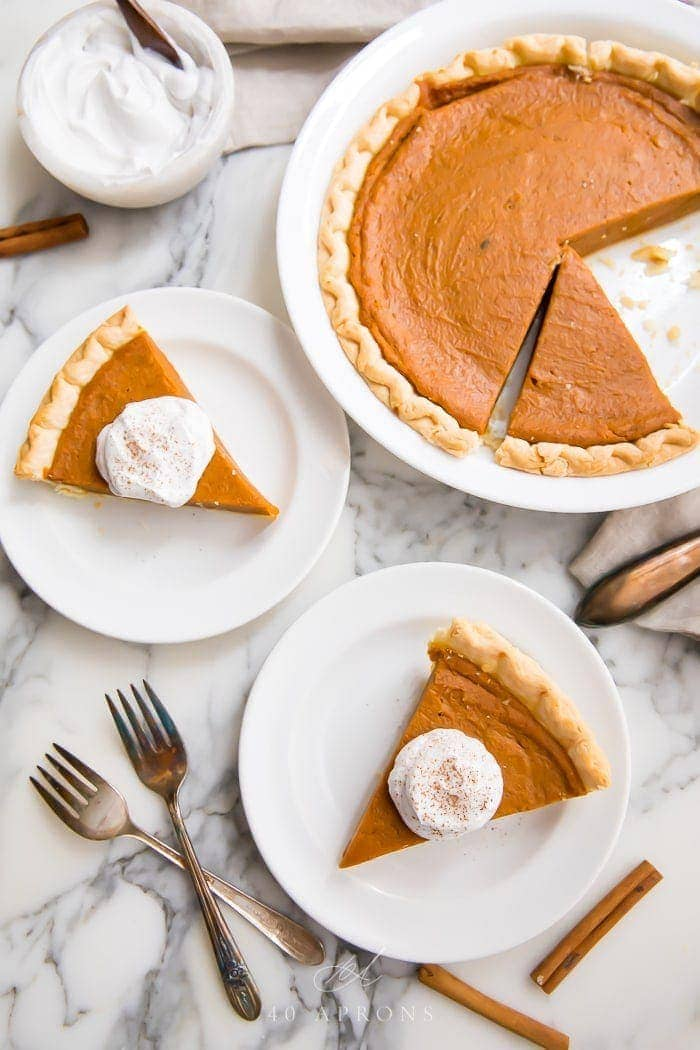 Slices of vegan pumpkin pie served with cream on white plates