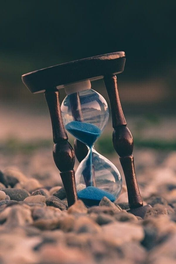 an hourglass filled with blue sand standing on pebbles