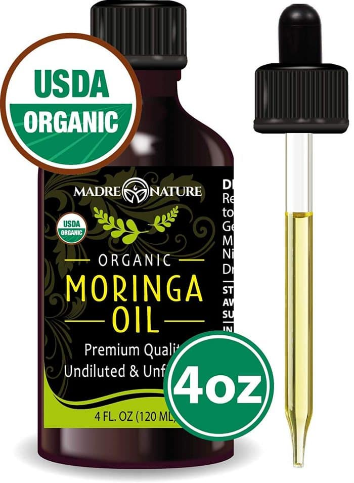 a small bottle of organic moringa body oil for dry winter skin against a white background