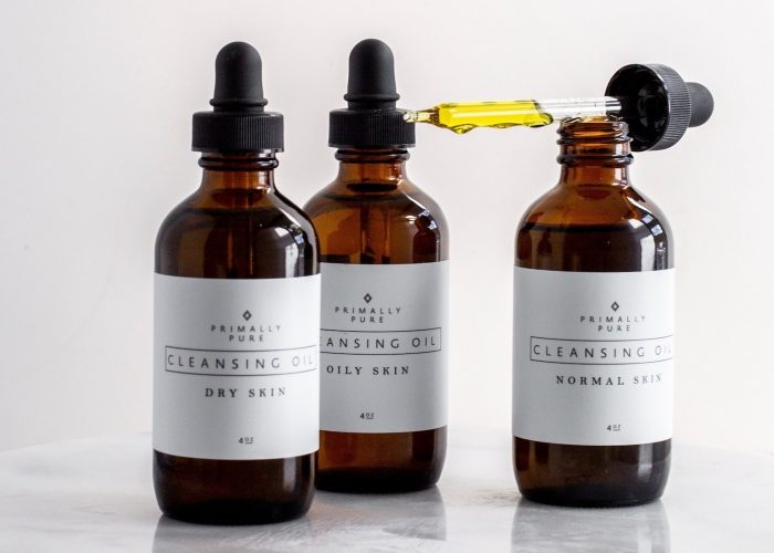 three bottles of Primally Pure cleansing oil against a white background
