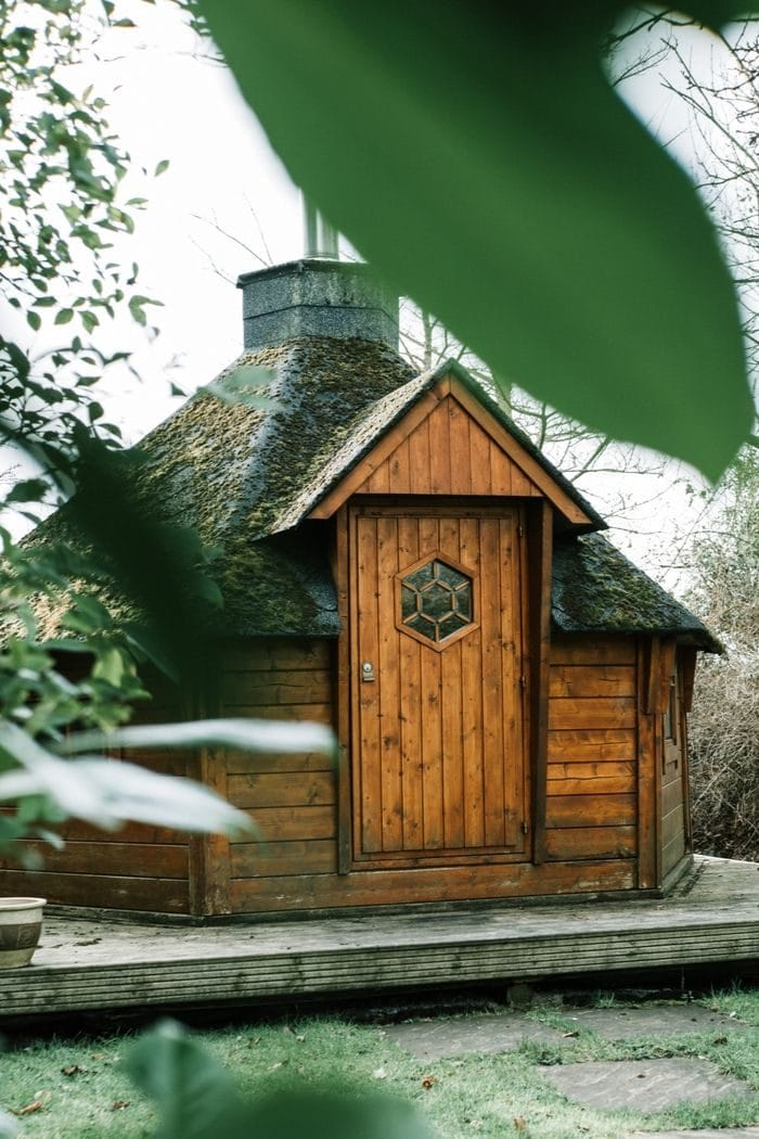 a small wooden Finnish sauna cabin in an autumnal garden