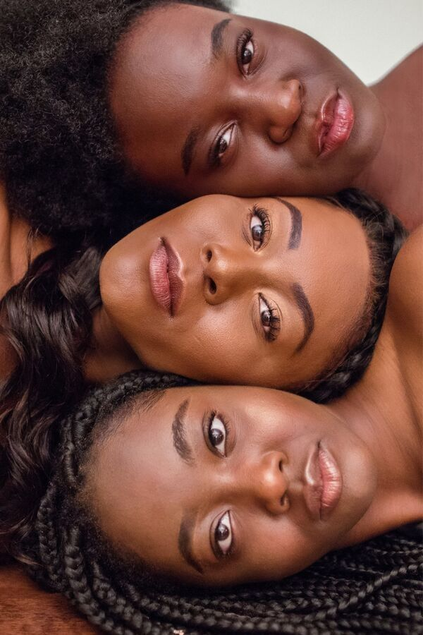 three dark skinned women with very clear skin lying next to each other in a line with their faces facing upwards