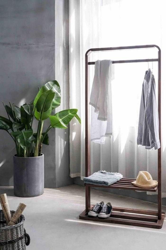 a minimalistic wardrobe with just the most basic items with a big plant next to the clothes rack