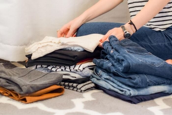a woman sorting through her wardrobe to declutter