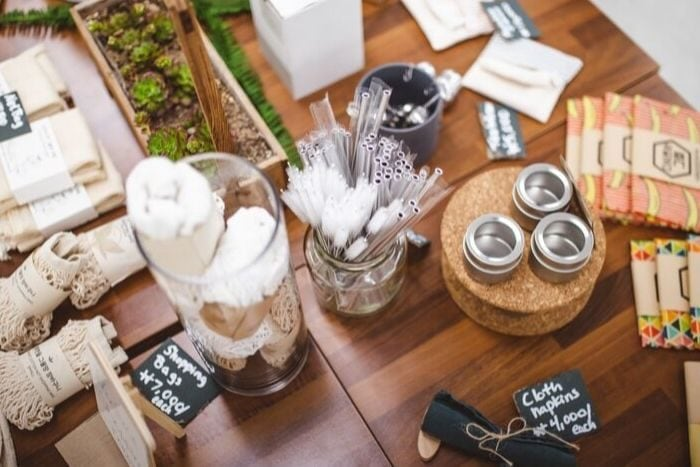 reusable food storage containers, metal straws and shopping bags displayed on the table of an eco store